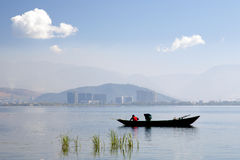 Fishermen on Lake in front of City Stock Photo