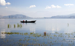 Fishermen on Lake in front of City Stock Photography