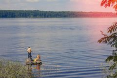 Fishermen on a large lake, summer sunny day stock images