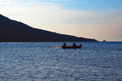 Fishermen Letting Out Net in Bay, Greece Royalty Free Stock Image