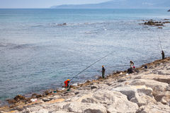 Fishermen with long rods stand on the coast of Atlantic ocean Royalty Free Stock Photos