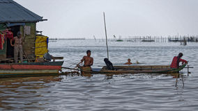 Fishermen in longboat, Tonle Sap, Cambodia. Fishermen in longboats next to floating huts at fishing village of Tonle Sap, Cambodia Royalty Free Stock Photography