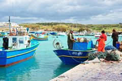 Fishermen on Luzzu colored boat at Marsaxlokk Harbor Malta. Marsaxlokk, Malta - April 5, 2014: Fishermen on Luzzu colored boat at Marsaxlokk Harbor, Malta island Stock Photography