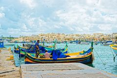 Fishermen on Luzzu colorful boat at Marsaxlokk Harbor Malta. Marsaxlokk, Malta - April 5, 2014: Fishermen on Luzzu colorful boat at Marsaxlokk Harbor, Malta Stock Images