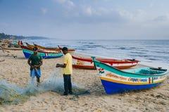 Fishermen mending net. Mahbalipuram, India - 02.10.2014: Fishermen mending the fishing net on Mahabalipuram beach Royalty Free Stock Photography