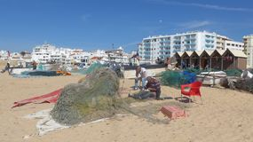Fishermen mending their nets. At the long, wide, fine sandy fisherman beach of Armacao de Pera, Algarve, Portugal. Any fishermen mending their nets. At the long Royalty Free Stock Image