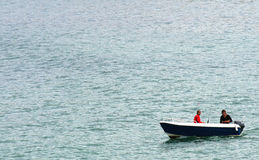 Fishermen in motorboat. Two fishermen in a motorboat on water stock images