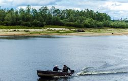Fishermen move in a motorboat through the water against a background of green trees and a blue sky. View of the Pripyat River: fishermen move in a motorboat stock photo