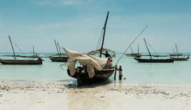 Fishermen near their boat on the shore, Zanzibar Stock Image