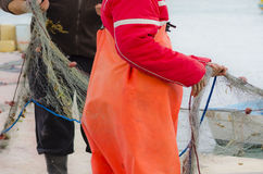 Fishermen pulling fishing net. Two fishermen pulling a fishing net stock image