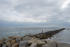 Fishermen on ocean break water on cloudy day. Anglers cast into the Pacific Ocean from rocks in San Pedro, south of Los Angeles, California royalty free stock image