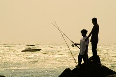 Fishermen On Rocks Stock Images