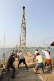 Fishermen operate a Chinese fishing net Royalty Free Stock Image