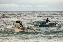 Fishermen Paddling Through a Rough Sea - Bohol, Philippines Stock Image