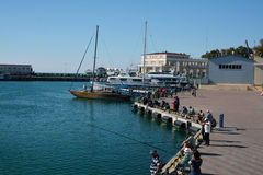 Fishermen and people watching the boats in the port Sochi Stock Image