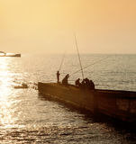 Fishermen on the pier on the background of sunset Stock Image