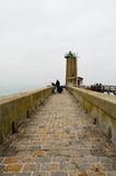 Fishermen on pier near a beacon light. On a cloudy day in Fecamp, France Stock Photos
