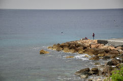 Fishermen on the pier by the sea. Fishermen on the dock at the Mediterranean Sea Stock Images
