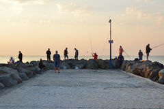 Fishermen on a pier at sunrise Stock Photography
