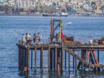 Fishermen on pier. Valparaiso, February 2011. People fishing on a pier in the bay with the city on background Royalty Free Stock Photo