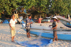 Fishermen preparing fish nets at sunset. Fishermen preparing fish nets at sunset on the beach of Jimbaran, Bali royalty free stock photos