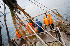 Fishermen in protective suits on deck Fishing vessel Stock Photo