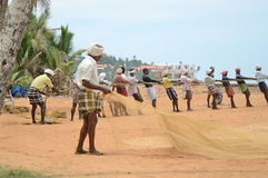 Fishermen are pulling the net from the sea in India. Royalty Free Stock Images