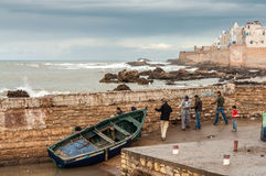 Fishermen pulling their boat out of the water Stock Image