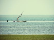 Fishermen pulling a traditional fishing boat off the coast of Mozambique Stock Photography