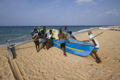 Fishermen pushing dugout canoe in Batticaloa, Sri Lanka Stock Photo