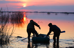 The fishermen put you in the boat. The fishermen put you in a boat on the river Pyshma, sunset, evening rustic idyll, harmony, spill on the river Royalty Free Stock Photo
