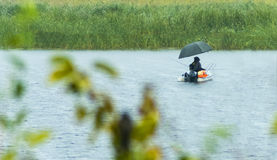 Fishermen at rainy weather royalty free stock photography