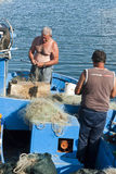Fishermen repairing fishing nets Stock Images