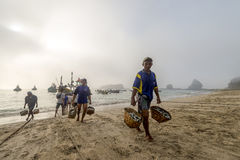 Fishermen return to shore after their catch Stock Photos
