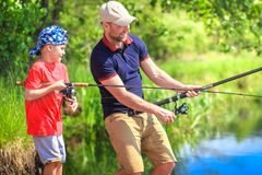 Fishermen on riverside with fishing rods. Father and son catching fish on lake shore. Family fishing stock image