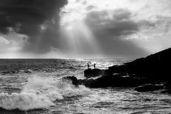 Fishermen on rocks. Fishermen fishing on rocks on seaside taking so much of risks Royalty Free Stock Images