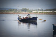 Fishermen in rowboat Stock Images