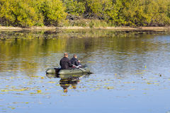 Fishermen rowing on an inflatable boat to catch predatory fish Stock Photo