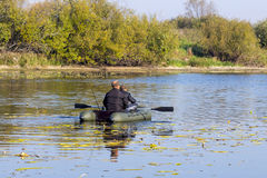 Fishermen rowing on an inflatable boat to catch predatory fish Royalty Free Stock Image