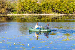 Fishermen rowing on an inflatable boat to catch predatory fish Stock Image
