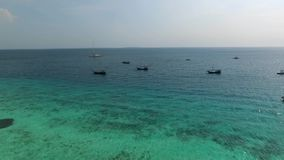 Fishermen`s boats near touristic beach in Zanzibar, aerial. Fishermen`s boats near the touristic beach in Zanzibar, Tanzania, clear blue waters, aerial stock video footage