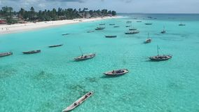 Fishermen`s boats near touristic beach in Zanzibar, aerial. Fishermen`s boats near the touristic beach in Zanzibar, Tanzania, clear blue waters, aerial stock footage