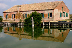 Fishermen's house reflected in the water. Large fishermen's house at the lake of Comacchio, Italy. The old orange house is reflected in the calm water on very Stock Photography
