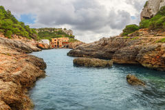 Fishermen`s houses in Cala s`Almonia, on the coast of Migjorn, S. Antanyi, Mallorca, Balearic Islands, Spain Stock Photos
