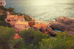 Fishermen`s houses in Cala s`Almonia, on the coast of Migjorn, S. Antanyi, Mallorca, Balearic Islands, Spain Stock Image