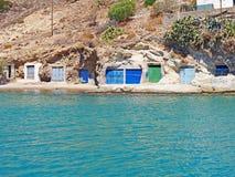 Fishermen`s huts carved into the rocky coast of Kimolos Island royalty free stock photos