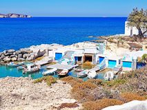 Fishermen`s huts carved into the rocky coast of Milos Island Royalty Free Stock Image