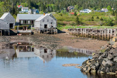 Fishermen`s sheds in the cove. Fishermen`s work sheds safely nestled in the harbour Stock Photo