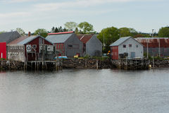 Fishermen`s sheds in the cove. Fishermen`s work sheds safely nestled in the harbour Royalty Free Stock Photos
