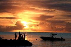 Fishermen's Sunset. Some of the locals go fishing off a rocky point in Dickenson Bay Royalty Free Stock Photography